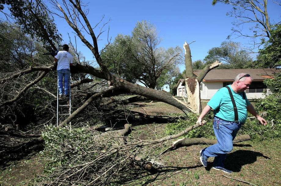 Tim Twardowski, left, and his cousin Raymond Greer help clear downed trees from the home of Twardowski's parents on Gebhardt Road on Wednesday in Sealy.  Many residents are still without power. Photo: Godofredo A. Vasquez, Staff / Godofredo A. Vasquez