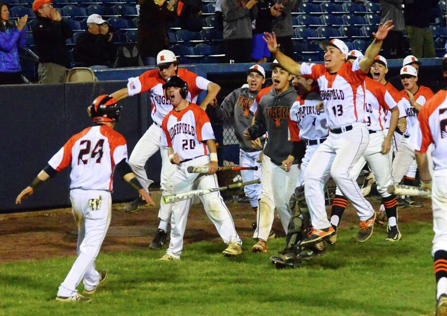 Ridgefield celebrates a run brought in by Colin Motill, left, during FCIAC baseball semi-finals action  against Trumbull at the Ballpark at Harbor Yard in Bridgeport, Conn., on Wednesday May 24, 2017. Photo: Christian Abraham / Hearst Connecticut Media / Connecticut Post