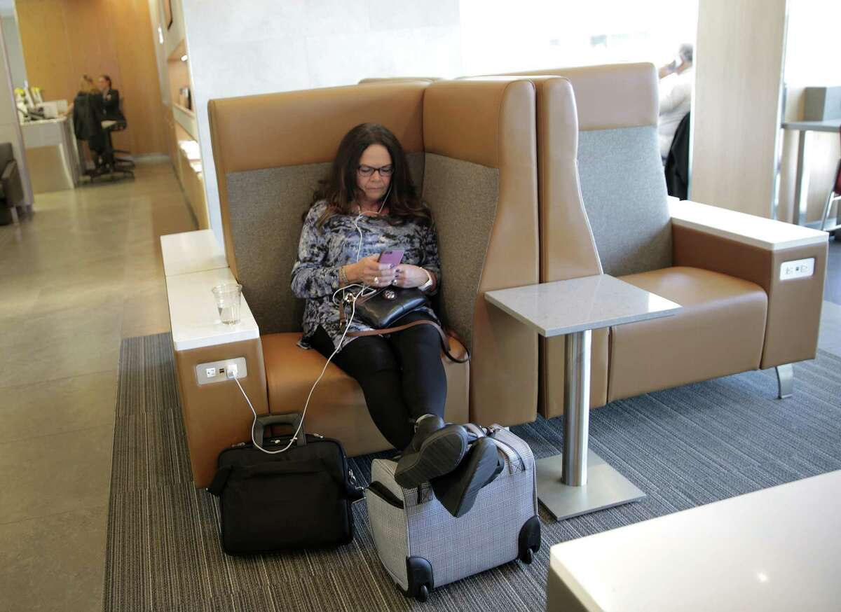 Barb Howlett of Syracuse, kicks back as she waits for her flight in new Admirals Club for American Airlines customers at Terminal A at IAH on Wednesday, May 24, 2017, in Houston. The club has its official opening June 12. ( Elizabeth Conley / Houston Chronicle )