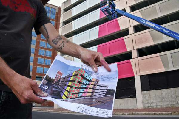 NYC street artist J Mikal David aka Hellbent shows the plan for his new mural commissioned for the Quackenbush garage Tuesday May 23, 2017 in Albany, NY.  (John Carl D'Annibale / Times Union)