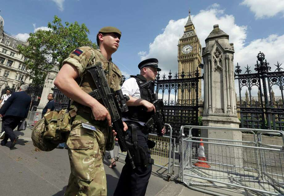 A member of the army joins police officers in Westminster, London, Wednesday, May 24, 2017. Britons will find armed troops at vital locations Wednesday after the official threat level was raised to its highest point following a suicide bombing that killed more than 20, as new details emerged about the bomber. (AP Photo/Tim Ireland) ORG XMIT: LLT106 Photo: Tim Ireland / Copyright 2017 The Associated Press. All rights reserved.