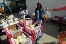 From left, Destiny Jackson, 9, Kennedy Andrews, 12 and Kendriana Andrews, 14, sack produce during the Southeast Texas Food Bank's drive on Tuesday. Senior citizens also registered for monthly food distributions in the Senior Box program.    Photo taken Tuesday, May 24, 2017 Guiseppe Barranco/The Enterprise