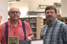 Longtime postal carrier Tommy Louthan (left) completed his final rounds Wednesday after a total of 30 years of service to the U.S. Postal Service. Prior to making his last deliveries, Louthan received a certificate and retirement gift in the form of a coin bank crafted incorporating a post office box door from Plainview Postmaster Mike Hodges. Before coming to the Plainview Post Office, Louthan worked out of the Hale Center Post Office, carrying Route 2.