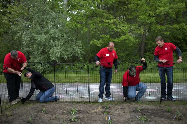 The Dow Chemical Co. employees from left: Dwayne Knapp, Chad Strydhorst, Scott Seeley, Chris Salinas and Rob Smith set-up a fence around gardens at Floyd Elementary Wednesday evening. Approximately 100 Dow employees and Floyd Elementary staff mulched gardens, planted fruit trees and built garden boxes for the school.