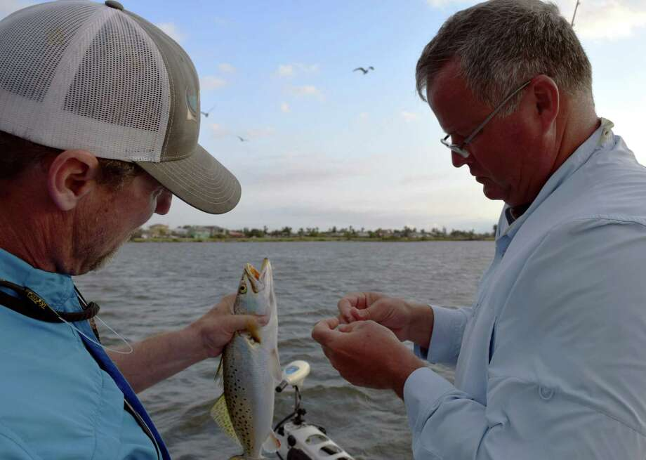 Guide Scott Hibbetts (left) and Corpus Christi angler Kevin Hagadorn unhook a nice spotted sea trout caught during an early morning, very windy trip near Bluff Landing Marina. Photo: Ralph Winingham / For The Express-News