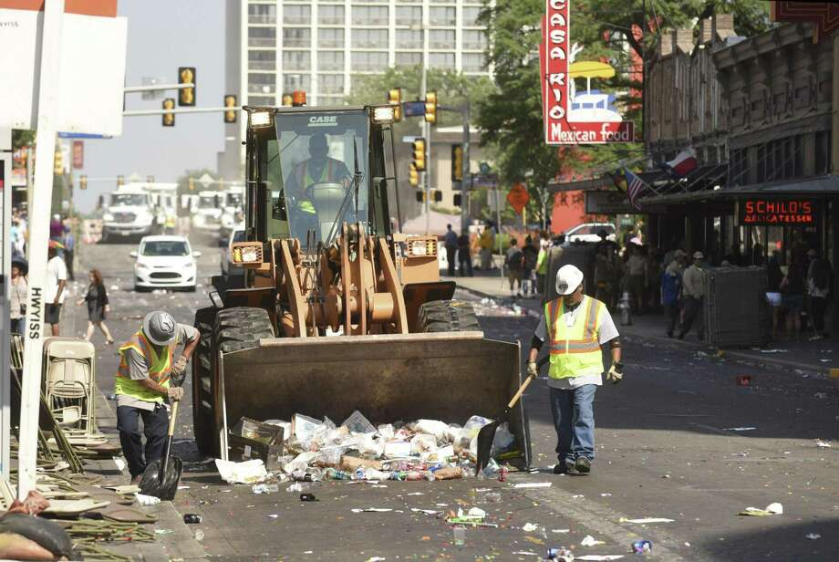 A clean-crew works on West Commerce minutes after the end of the Battle of Flowers Parade on Friday, April 28, 2017. Photo: Billy Calzada /San Antonio Express-News / San Antonio Express-News