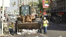 A clean-crew works on West Commerce minutes after the end of the Battle of Flowers Parade on Friday, April 28, 2017.