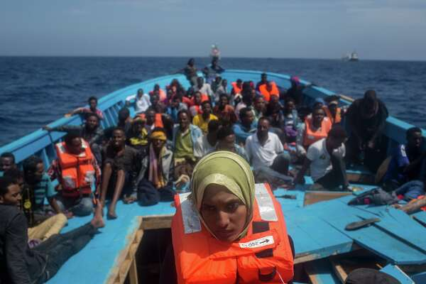 Refugees and migrants are seen on board a wooden boat as they wait for rescue crews from the Migrant Offshore Aid Station (MOAS) 'Phoenix' vessel on May 24, 2017 off Lampedusa, Italy. The Migrant Offshore Aid Station (MOAS) 'Phoenix' vessel rescued 603 people after one of three wooden boats partially capsized leaving more than 30 people dead. Numbers of refugees and migrants attempting the dangerous central Mediterranean crossing from Libya to Italy has risen since the same time last year with more than 43,000 people recorded so far in 2017. In an attempt to slow the flow of migrants Italy recently signed a deal with Libya, Chad and Niger outlining a plan to increase border controls and add new reception centers in the African nations, which are key transit points for migrants heading to Italy. MOAS is a Malta based NGO dedicated to providing professional search-and-rescue assistance to refugees and migrants in distress at sea. Since the start of the year MOAS have rescued and assisted 3572 people and are currently patrolling and running rescue operations in international waters off the coast of Libya.  (Photo by Chris McGrath/Getty Images)