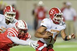 Walter White (14) of the Stafford Spartans runs up the middle in the second half against the Stafford Spartans in a high school football Class 4A, Division 1 Regional Semifinal on Friday, November 25, 2016 at Maddry Stadium in Channelview Texas.