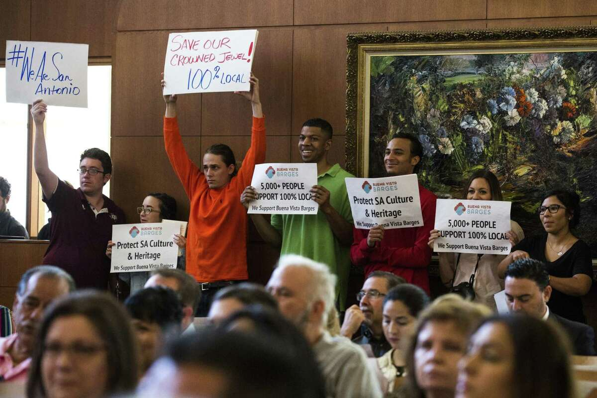 People held up signs during a city council meeting at Municipal Plaza building in San Antonio, Texas on May 25, 2017. Ray Whitehouse / for the San Antonio Express-News