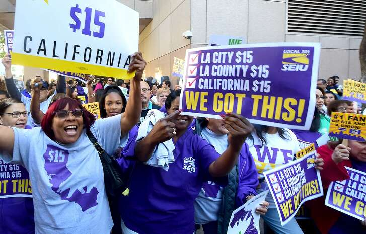 Workers celebrate outside the Ronald Reagan State Building in downtown Los Angeles, where California Governor Jerry Brown signed the bill that will raise the state's minimum wage to $15 an hour by 2022 while surrounded by supporters and politicians in Los Angeles, California on April 4, 2016. / AFP PHOTO / FREDERIC J. BROWNFREDERIC J. BROWN/AFP/Getty Images