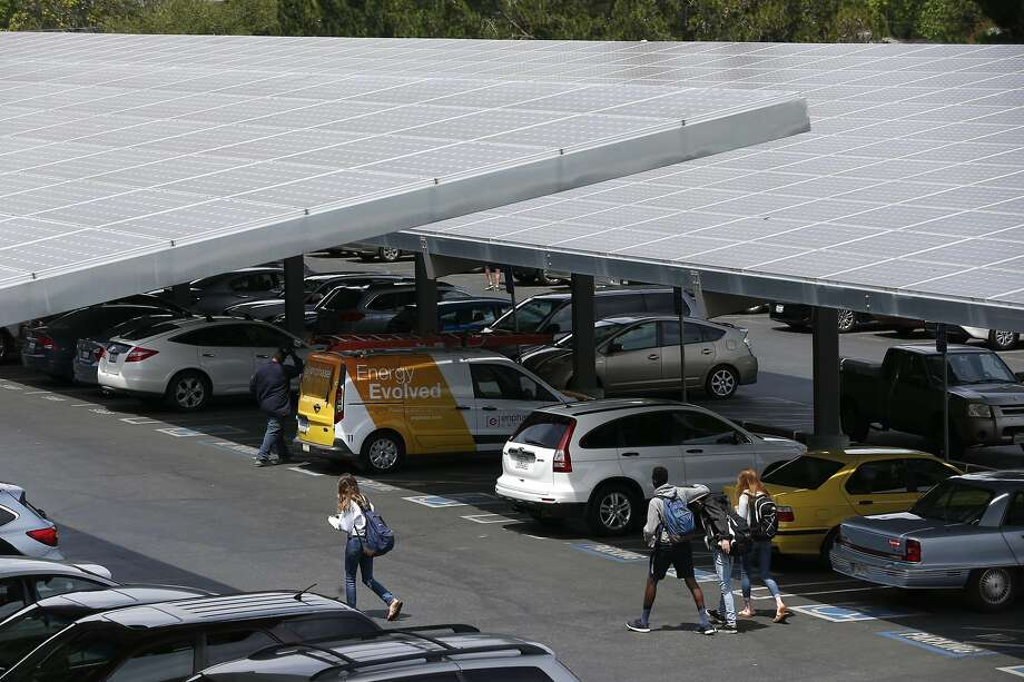 Solar panels cover the parking lot at Los Altos High School, above, where Ronnie Garcia (left) and Keith Mitchell, below, perform   maintenance on energy-storage batteries.   A state bill would offer financial incentives for installing such batteries. Photo: Paul Chinn, The Chronicle