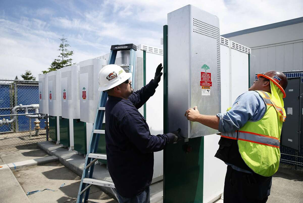Ronnie Garcia (left) and Keith Mitchell complete routine maintenance on large battery units installed at Los Altos High School in Los Altos, Calif. on Wednesday, May 24, 2017. Some state officials are hoping that a financial incentive program, similar to the solar panel rebates offered to homeowners, would spark growth in the battery industry and lower costs.
