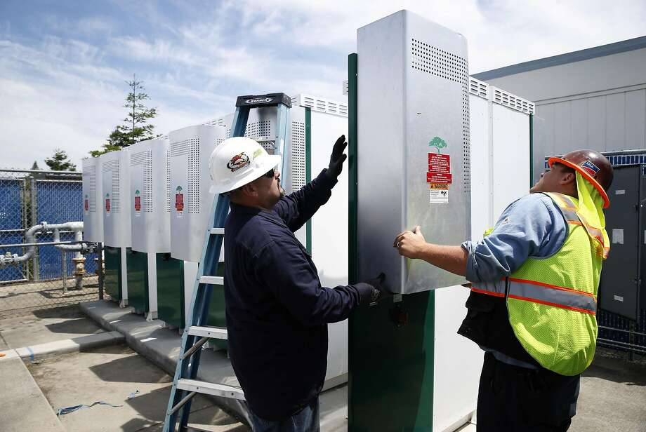 Ronnie Garcia (left) and Keith Mitchell complete routine maintenance on large battery units installed at Los Altos High School in Los Altos, Calif. on Wednesday, May 24, 2017. Some state officials are hoping that a financial incentive program, similar to the solar panel rebates offered to homeowners, would spark growth in the battery industry and lower costs. Photo: Paul Chinn, The Chronicle