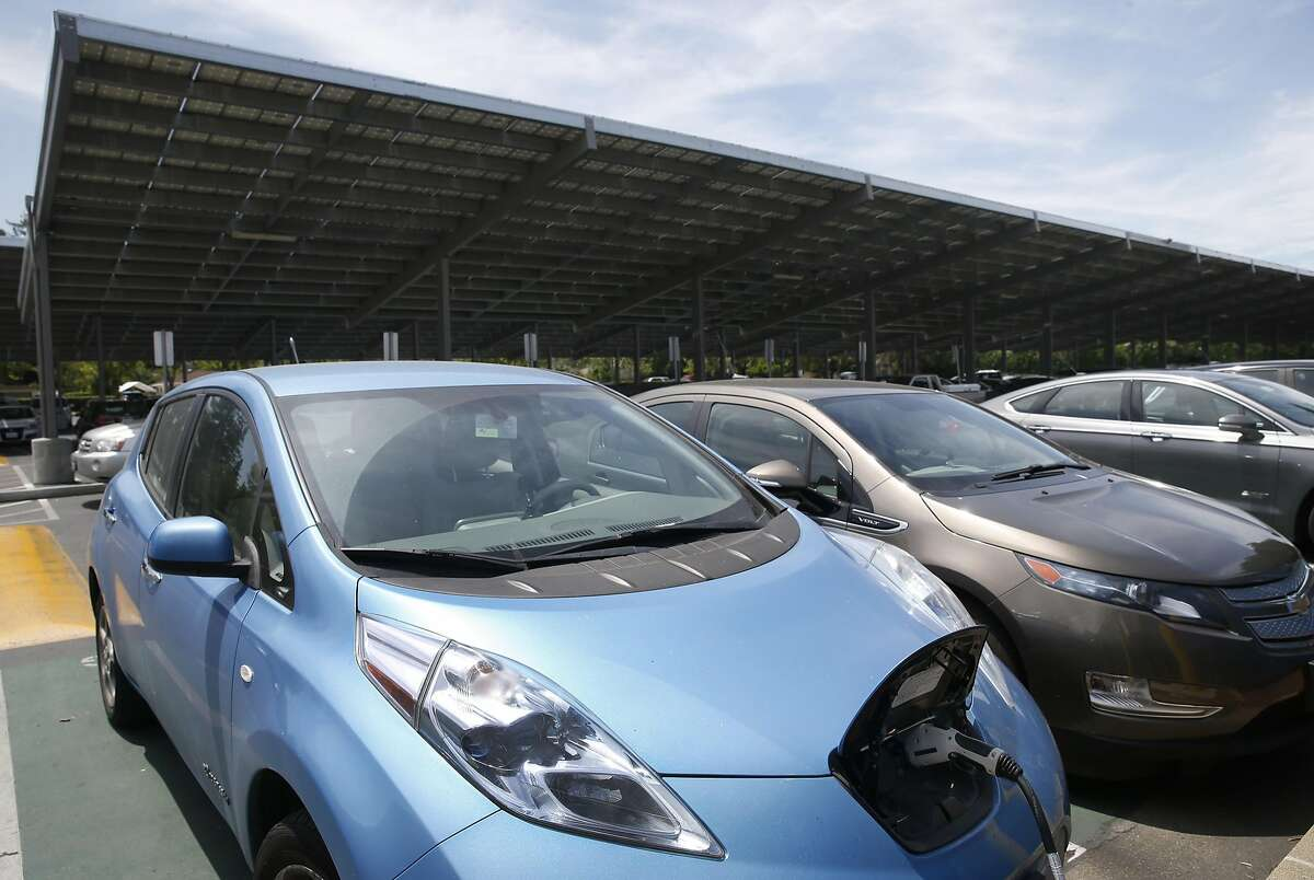 Electric vehicles are plugged in to charging stations in a parking lot with solar panels at Los Altos High School in Los Altos, Calif. on Wednesday, May 24, 2017. Some state officials are hoping that a financial incentive program, similar to the solar panel rebates offered to homeowners, would spark growth in the battery industry and lower costs.