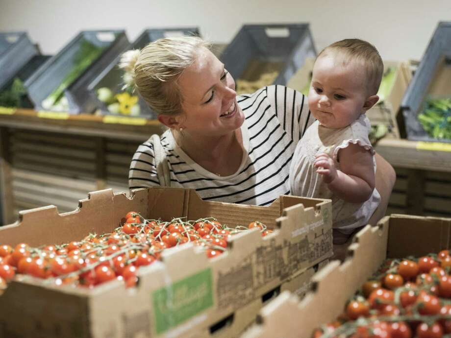 Meg Walker lets her daughter Campbell, 9 months old, pick up a cherry tomato from Trukin' Tomato during the midweek market, a local farmers market generally for wholesalers but open to the public on Wednesdays. Photo: Matthew Busch /For The Express-News / © Matthew Busch
