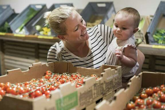 Meg Walker lets her daughter Campbell, 9 months old, pick up a cherry tomato from Trukin' Tomato during the midweek market, a local farmers market generally for wholesalers but open to the public on Wednesdays.