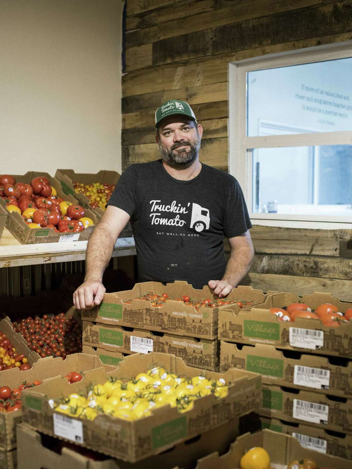 Bryan Pape of Trukin' Tomato poses for a portrait along with his produce for sale during the midweek market.