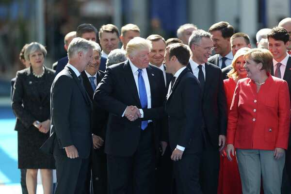 President Trump, center left, shakes hands with Emmanuel Macron, France's president, as other world leaders look on during a summit of world leaders at the North Atlantic Treaty Organization (NATO) in Brussels Thursday.
