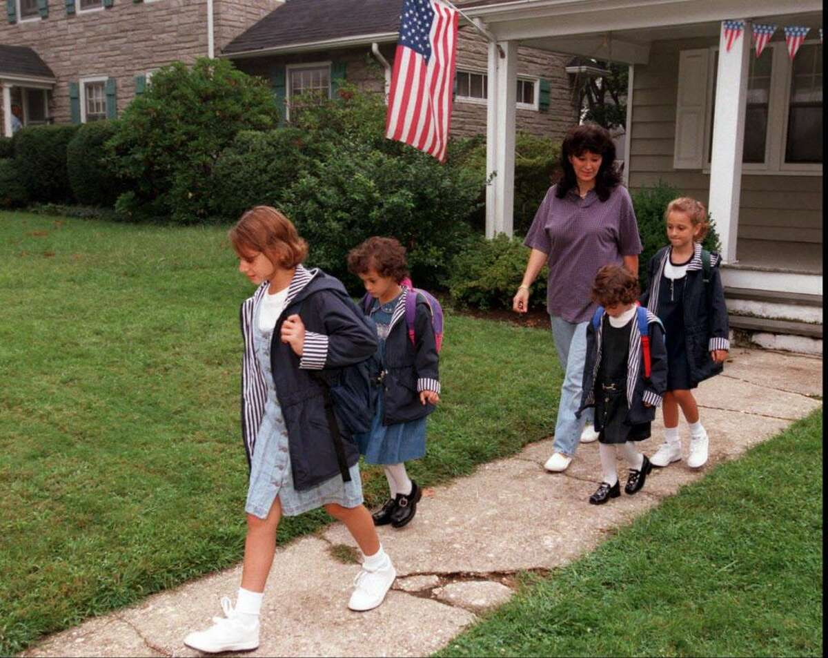 Linda Kuzlik on Sept. 2, 1997 with five adopted Hungarian children she sent them off to school in Stamford yesterday. The older boy, Ron, left early for Rippowam. This week, the family celebrates the 20th anniversary of the children becoming Kuzlik's. Tom Ryan/Staff Photo