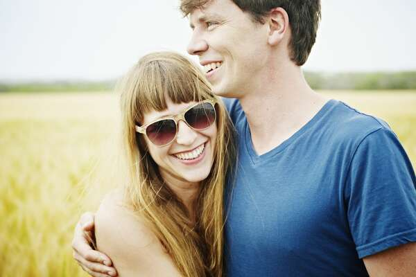 Couple standing in wheat field embracing smiling woman wearing sunglasses
