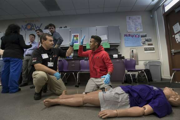 Brandon Bond, an EMT congratulates student Dez Fraiser after he demonstrates how to stop the bleeding of a midline thigh wound, saving the victim's life at Sequoia Union High on Thursday, May 25, 2017 in Redwood City, CA