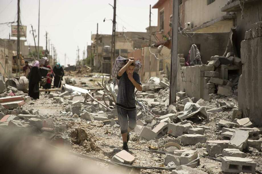 An Iraqi boy carries heavy belongings through rubble as he flees fighting between Iraqi special forces and Islamic State militants, in western Mosul, Iraq, Monday, May 15, 2017. (AP Photo/Maya Alleruzzo) Photo: Maya Alleruzzo, STF / Associated Press / Copyright 2017 The Associated Press. All rights reserved.