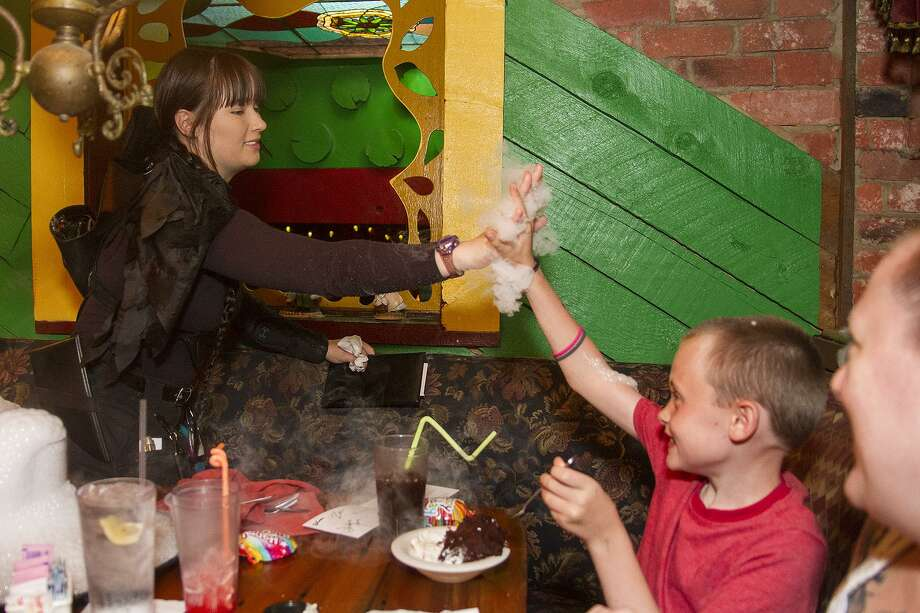 Kimberly Sinclair, in character as Katniss Everdeen, gives a high five to birthday boy Benjamin Loughran, 8, at the Magic Time Machine. Photo: Alma E. Hernandez /For The San Antonio Express News