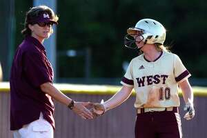 Magnolia West head coach Sheryl Tamborello gives Emma McBride a high-five after stealing third during the first inning of a District 20-5A high school softball game, Friday, April 21, 2017, in Magnolia.