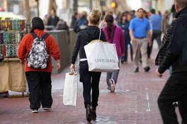 Pedestrians carry shopping bags as they walk along Market Street in San Francisco, California, U.S., on Thursday, Jan. 5, 2012. Photographer: David Paul Morris/Bloomberg