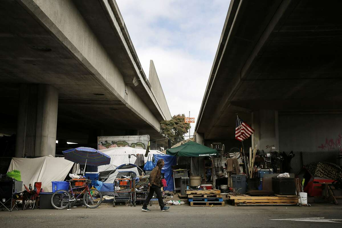 A man, who only gave his first name as Jim, walks back to his encampment after grabbing his friends cigarette lighter near Brush and 6th streets on Thursday, May 25, 2017, in Oakland, Calif. They're seen the encampment grown to more than a couple dozen people in the last four years.