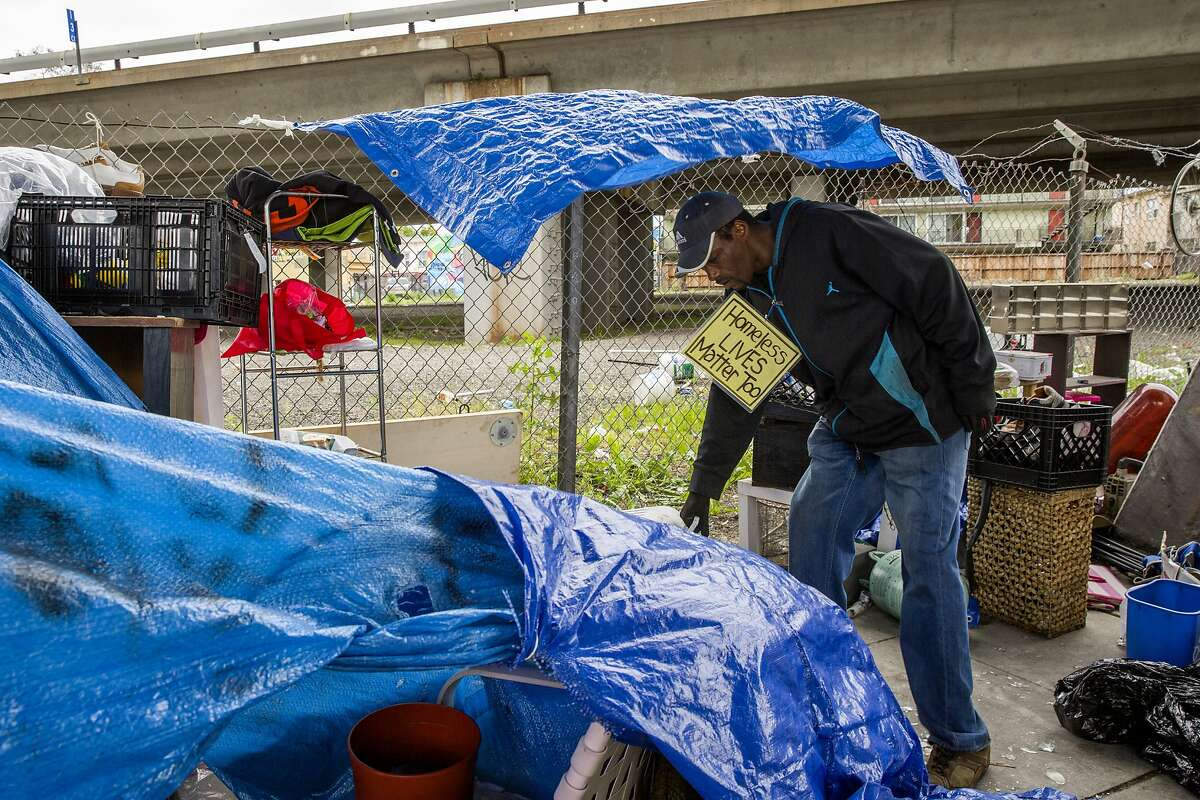 Sean Moses begins to clear his belongings as city officials prepare to clean the sidewalk of a homeless encampment near 27th Street and Northgate Avenue on Thursday, May 25, 2017, in Oakland, Calif. Moses said he's lived at the encampment for three years and has seen the homeless population grow in the area.