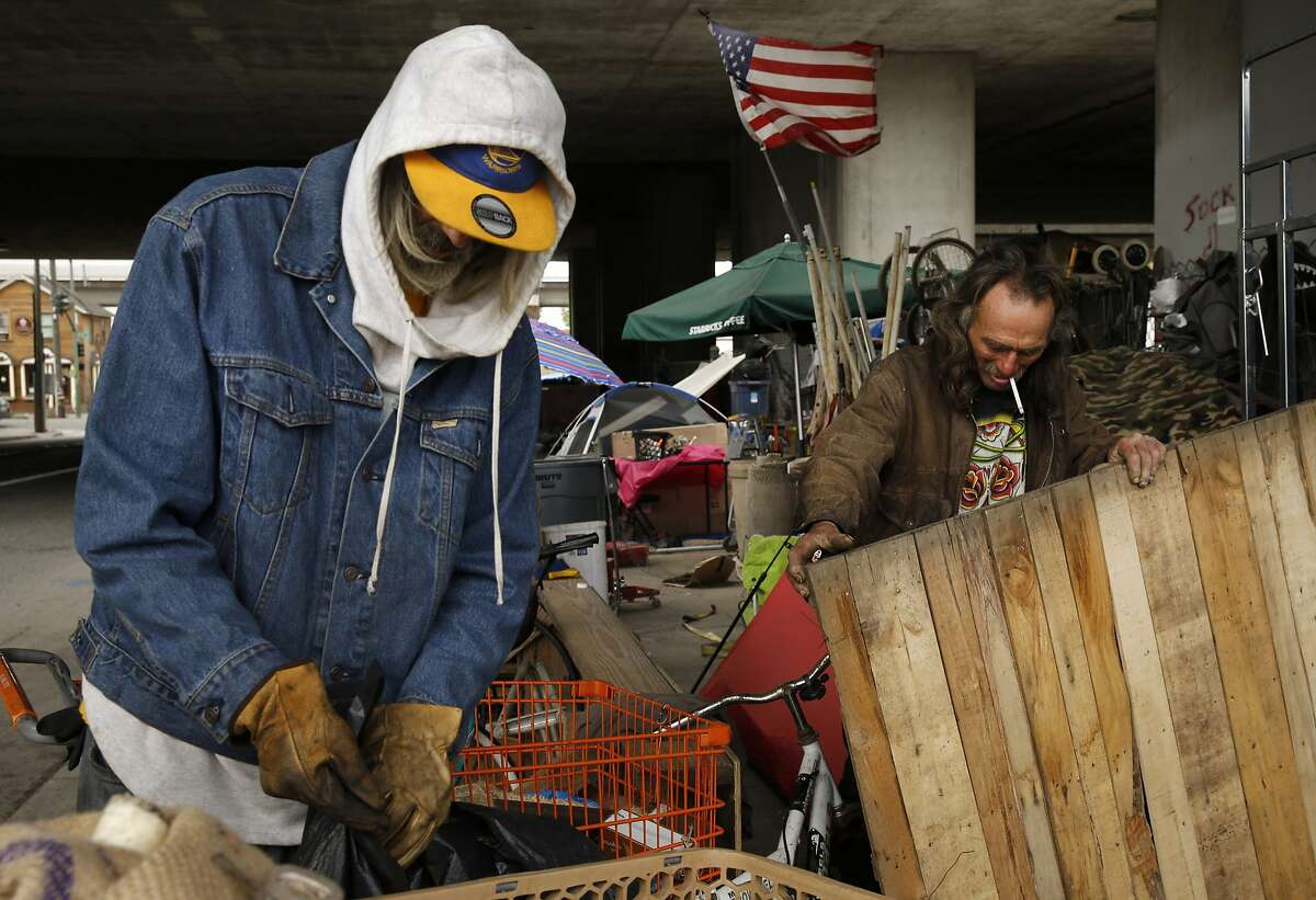From left: Army veteran Bill Davidson checks his finds of the day as a man who gave his name as Jim reinforces his tent area against rodents at their encampment near Brush and 6th streets on Thursday, May 25, 2017, in Oakland, Calif. Jim and Davidson said they were the first ones to set a tent up at the block. They've seen the encampment grow to more than a couple dozen people in the last four years.