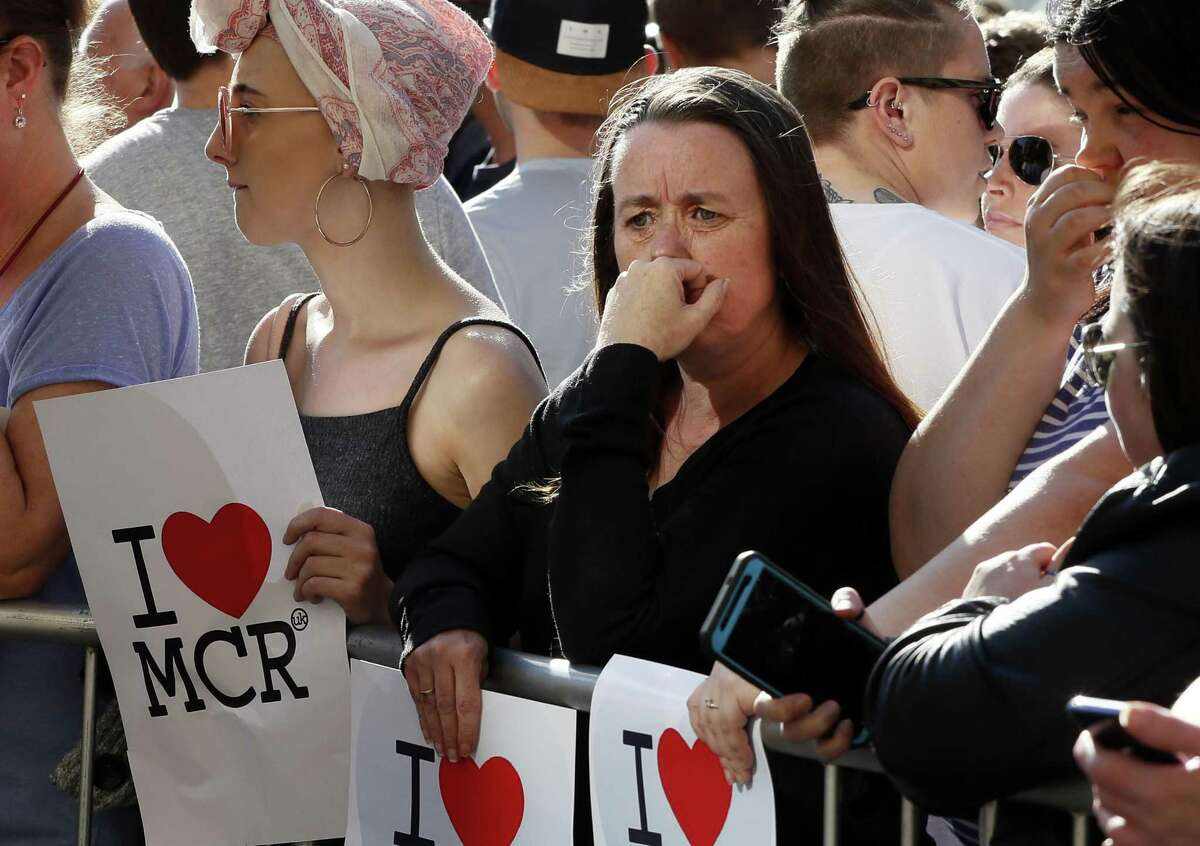 People attend a vigil in Albert Square, Manchester, England, Tuesday, the day after the suicide attack at an Ariana Grande concert that left 22 people dead as it ended on Monday night.