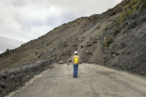 Bret Haney, construction inspector with Caltrans, looks at the south side of a landslide on Wednesday, May 24, 2017, after a massive slide went into the Pacific Ocean over the weekend in Big Sur, Calif. The slide buried a portion of Highway 1 under a 40-foot layer of rock and dirt and changed the coastline below to include what now looks like a rounded skirt hem, Susana Cruz, a spokeswoman with the California Department of Transportation, said Tuesday. (Joe Johnston/The Tribune (of San Luis Obispo) via AP)