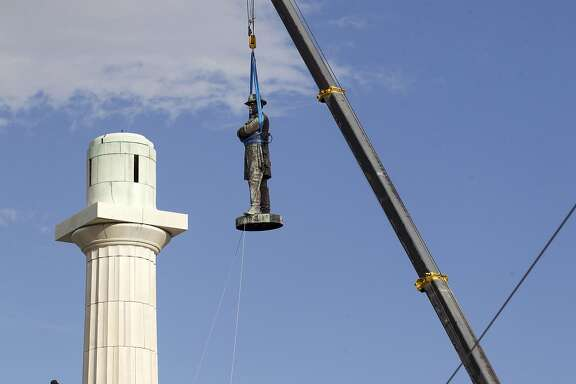 A statue of Confederate General Robert E. Lee is removed Friday, May 19, 2017, from Lee Circle in New Orleans. The city council voted to remove the monument and three other Confederate and white supremacist monuments in Dec. 2015. An obelisk honoring the militia known as the White League was taken down in April; a statue of Confederate President Jefferson Davis was removed May 11; and a statue of Confederate General P.G.T. Beauregard was taken down on Wednesday. (AP Photo/Scott Threlkeld)
