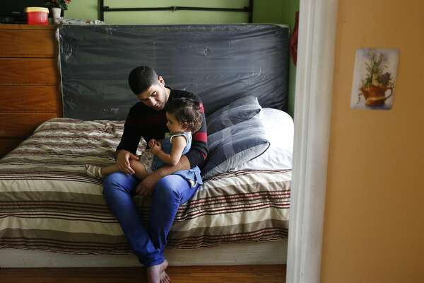 Mohanad Hussien, 23, sits on the bed with his daughter Nisreen Hussien, 1, in the family apartment Oct. 20, 2016 in Oakland, Calif. The Syrian family has recently been resettled in Oakland after spending a few years in Jordan after fleeing the Syrian civil war.