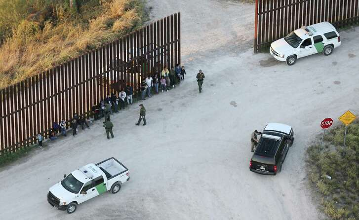 U.S. Border Patrol agents detain a group of immigrants, including children, by the U.S.-Mexico border wall near Penitas, Texas, Tuesday, Oct. 4, 2016. Also seen is a unit with the Texas Department of Public Safety.