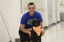 Stafford High School junior AJ Schalk, who has type 1 diabetes, has been attending class with his service dog Alpha for the past year after Stafford County school officials approved the idea. Alpha can tell when Schalk's blood sugar is askew by scent and gives Schalk a paw to warn Schalk. (Peter Cihelka /The Free Lance-Star via AP)