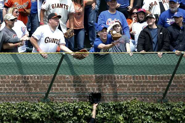 San Francisco Giants' Mac Williamson is unable to catch a home run by Chicago Cubs' Kris Bryant, as a fan catches the ball in the left field bleachers, during the first inning of a baseball game Thursday, May 25, 2017, in Chicago. (AP Photo/Charles Rex Arbogast)