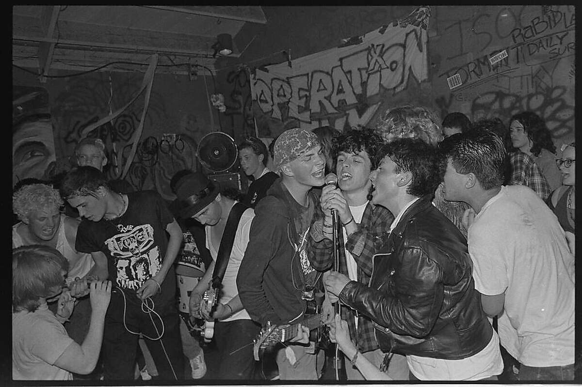 Billie Joe Armstrong (on microphone) sings with members of Operation Ivy at a 1988 show at 924 Gilman.