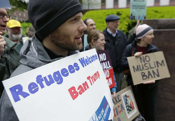 "Miles Treakle, left, of Seattle, holds a sign that reads ""Refugees Welcome Ban Trump,"" as he protests against President Donald Trump's revised travel ban, Monday, May 15, 2017, outside a federal courthouse in Seattle. A three-judge panel of the 9th U.S. Circuit Court of Appeals heard arguments Monday in Seattle over Hawaii's lawsuit challenging the travel ban, which would suspend the nation's refugee program and temporarily bar new visas for citizens of Iran, Libya, Somalia, Sudan, Syria and Yemen. (AP Photo/Ted S. Warren)"