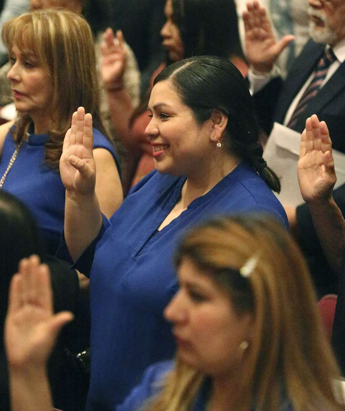 Benita Holguin (center), takes an oath of citizenship at Thursday's naturalization ceremony. In 2012, she became the first undocumented person to speak at a national convention of a major political party.