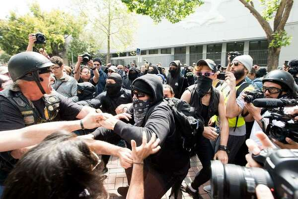 Protesters for and against President Donald Trump brawl on Saturday, April 15, 2017, in Berkeley, Calf.