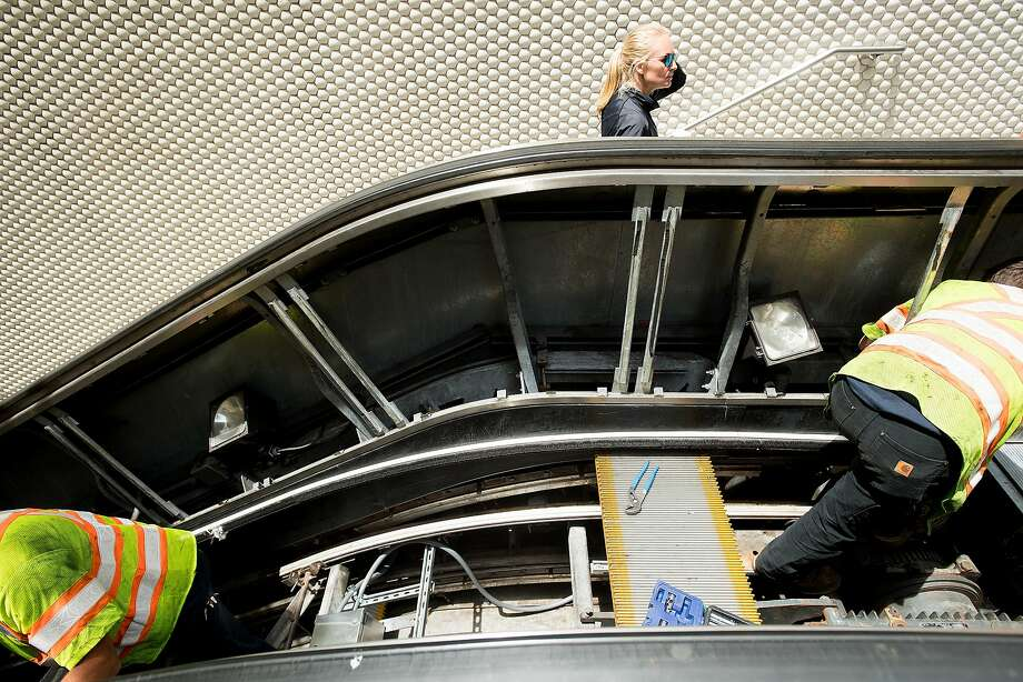 A BART passenger climbs the stairs as workers fix an escalator at Montgomery Street Station, one of the transit system's worst stations for escalator reliability. Heavy use, debris, vandalism and the elements take a big toll on the aging escalators. Photo: Noah Berger, Special To The Chronicle