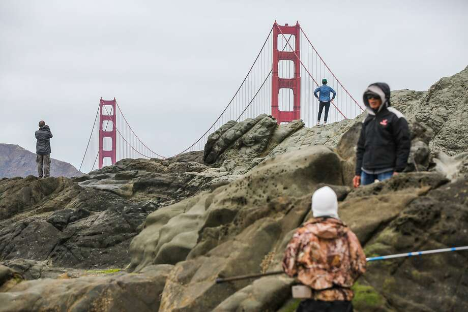 Leah Henry (top, blue) takes in the view of the Golden Gate Bridge from Baker Beach in San Francisco, California, on Wednesday, May 24, 2017. Photo: Gabrielle Lurie, The Chronicle