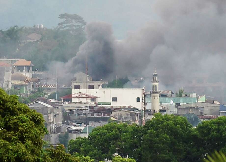 Smoke rises near a public market after military attack helicopters fired rockets on the positions of Muslim extremists  in the Philippine city of Marawi. Military forces bombed residential areas as they battled the Islamist militants.  Photo: TED ALJIBE, Staff / AFP or licensors