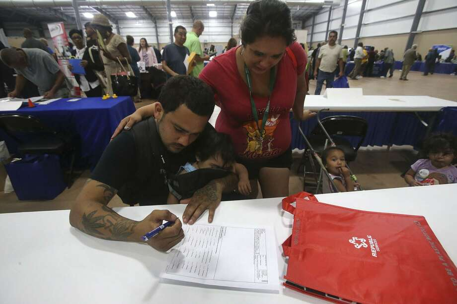 Christopher Hernandez fills out a job application with Ylora (cq) Posada Thursday May 25, 2017 during the Bexar County Second Chance Job Fair held at the Freeman Expo Hall. There were opportunities available in a variety of industries including hospitality, food service, construction, electrical, flooring, information, transportation, warehousing, assembly, automotive, telemarketing, and trucking. The fair featured businesses that are committed to hiring formally incarcerated local residents from all education and skill levels. Photo: John Davenport, STAFF / San Antonio Express-News / ©John Davenport/San Antonio Express-News