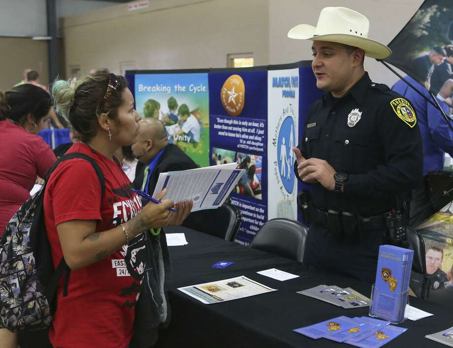 Gracie Castillo (left) inquires about job opportunities with the Bexar County Sheriff's office from deputy John Rivera (right) during  a Bexar County Second Chance Job Fair held at the Freeman Expo Hall. There were opportunities available in a variety of industries including hospitality, food service, construction, electrical, flooring, information, transportation, warehousing, assembly, automotive, telemarketing, and trucking. Photo: John Davenport /San Antonio Express-News / ©John Davenport/San Antonio Express-News