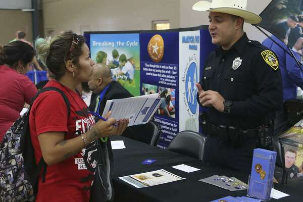 Gracie Castillo (left) inquires about job opportunities with the Bexar County Sheriff's office from deputy John Rivera (right) during  a Bexar County Second Chance Job Fair held at the Freeman Expo Hall. There were opportunities available in a variety of industries including hospitality, food service, construction, electrical, flooring, information, transportation, warehousing, assembly, automotive, telemarketing, and trucking.